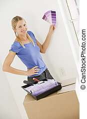 Woman with paint swatches in new home smiling