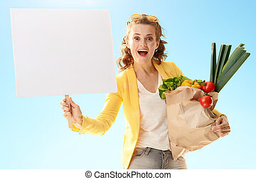 woman with paper bag with groceries showing blank poster against blue sky