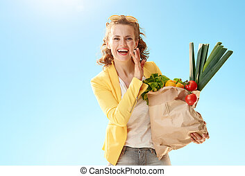 woman with paper bag with groceries telling exciting news against blue sky