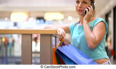 Woman with paper bags talking on a smartphone in a shopping center
