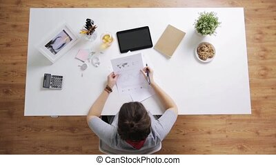 woman with papers and calculator at home office