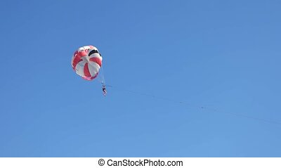 Woman with parachute. Blue sky background.