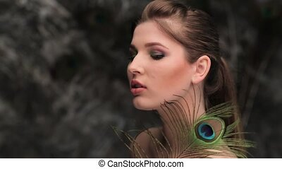 woman with peacock feather flirting in front of the camera