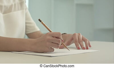 Woman with pencil writing on paper