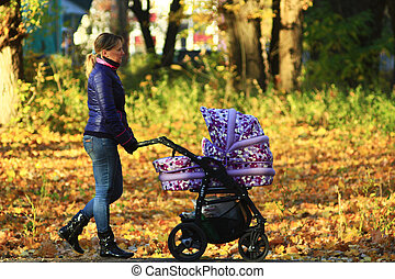 woman with perambulator in the park