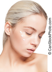 Woman with perfect skin and drops of cream on face