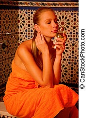 woman with perfume in hand in the bathroom