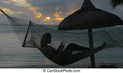 Woman with phone lying in hammock on the beach