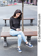 Woman with phone on the bench