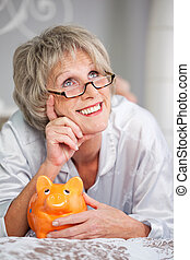 Woman With Piggybank Looking Up While Lying On Bed