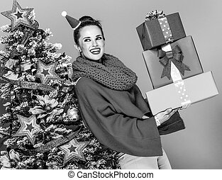 woman with pile of Christmas present boxes looking at copy space