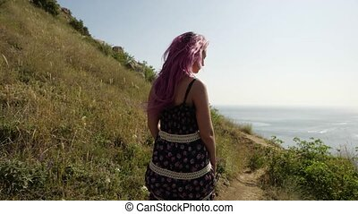 A woman of non-standard appearance with pink hair in a sundress with a floral print, walks along a narrow path on the slope of the mountain heading, before her opens an epic landscape on the coast