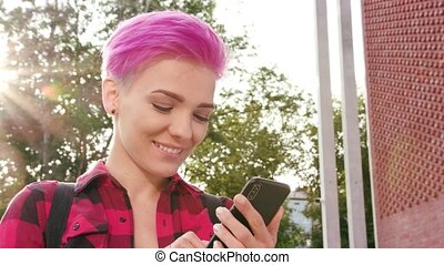 Woman with Pink Short Hair Using a Phone in Town - A young...