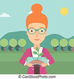 Woman with plant growing in bottle.