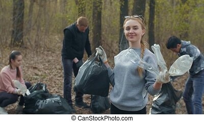 Woman with plastic trash and people collecting garbage on background