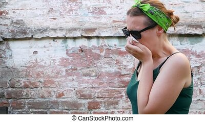 Woman with pollen allergy symptom smelling air with nose standing on brick wall background. Young sick girl sneezing, blowing her nose into handkerchief, using nasal spray against allergic rhinitis.