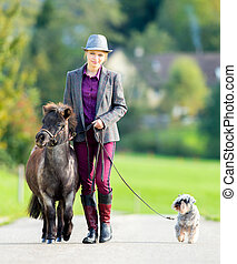 Woman with pony and dog - Woman walking with small pony and...