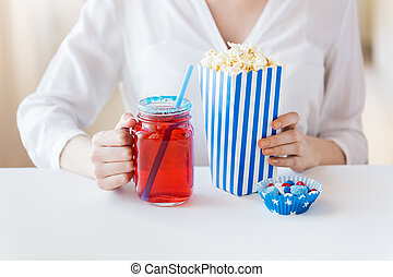woman with popcorn and drink in glass mason jar