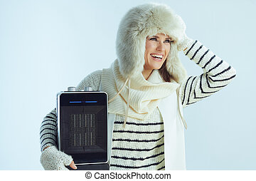 woman with portable electric heater looking at copy space