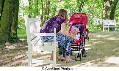 Woman with Pram Sitting on the Bench in the Park