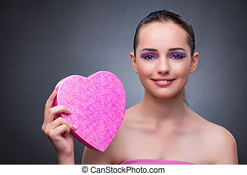 Woman with present in heart shaped box