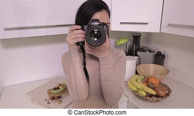 Woman with professional camera take pictures in kitchen
