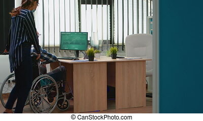Business woman with protection mask helping disabled man in wheelchair to get at desk, working in new normal in corporate office during coronavirus pandemic. Businesspeople respecting social distance