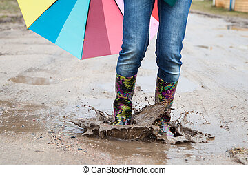 Woman with rain boots jumps into a puddle