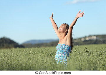 Woman with raised arms in a green meadow enjoying the wind ...