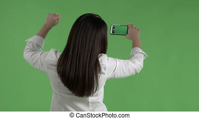 woman with raised fist taking pictures with camera phone against a green screen