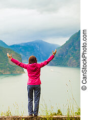 Woman with raised hands in norwegian mountains fjords -...