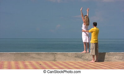 woman with raised hands near sea, man holds her