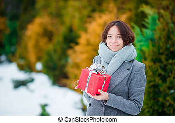 Woman with red christmas box gift in winter day outdoors