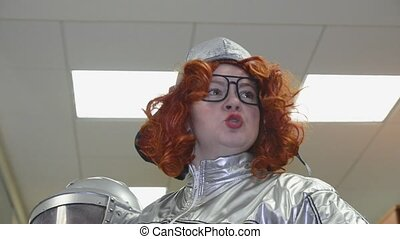 Woman with red curly hair in grey space suit, glasses...