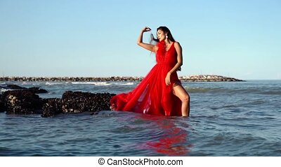 Woman with red dress in sea water