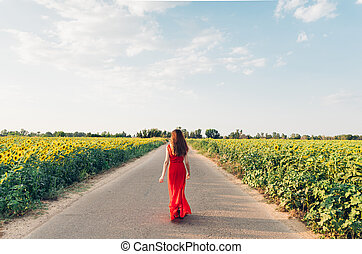 woman with red dress walking on road with sunflowers.