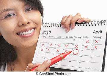 Woman with red felt tip pen and calendar, actually can be concept to get pregnant from its series, maybe can be used for US tax day