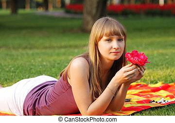 Woman with red flower in park