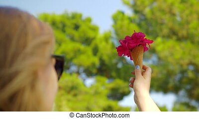 Woman with red flowers bouquet in waffle cone outdoor -...