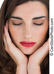 Woman with red lips with her eyes closed while leaning on...