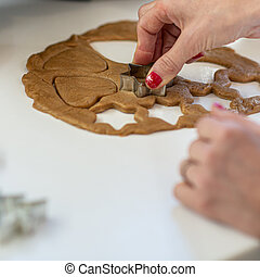 Woman with red painted nails making home made cookies