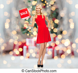 woman with red sale sign over christmas lights
