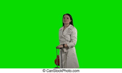 Woman with red umbrella and suitcase waving to taxi against a green screen