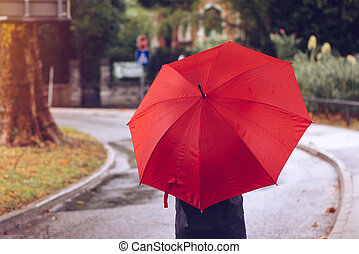 Woman with red umbrella walking on the street