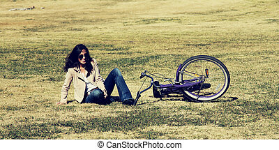 woman with retro bicycle in a park on early spring time