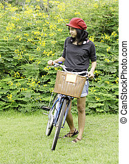 Woman with retro bicycle in a park