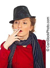 Woman with retro hat smoking