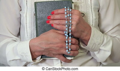 Woman with rosary and Holy Bible close up
