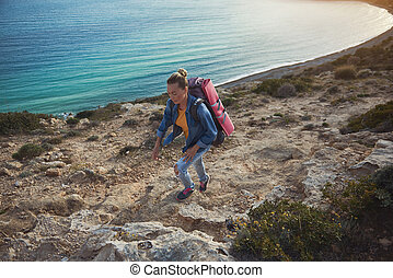 Woman with rucksack climbing hill - Female tourist with...