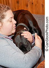Woman with sad face presses a large black dog to her chest